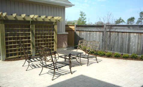 a fairly simple patio is boldly decorated with a faux pergola panel.