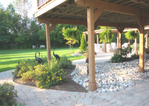 Area under a tall overhead deck transformed with stone, pavers, plants and statuary.